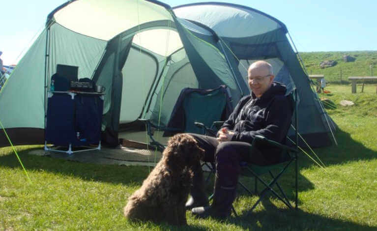 Man and his dog sitting next to his tent